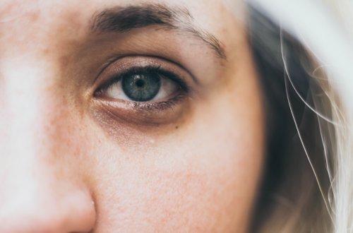 Inspiration: Junge Frau, die den Betrachter des Bildes erschöpft und mit Schmerz in den Augen direkt anblickt.